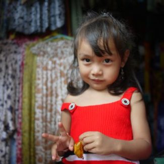 Balinese girl gives peace sign in Ubud Market
